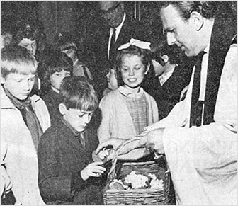 Photograph of Revd Derek Hole distributing primroses Mothering Sunday 1968 with Mr J R Loake (churchwarden) in the background