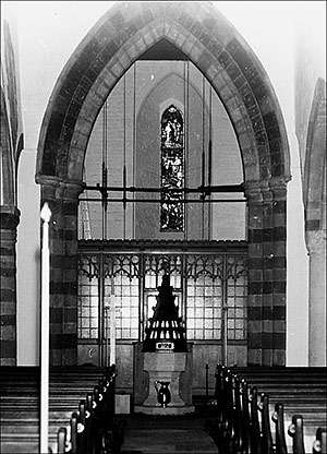 Photograph of church interior view to the west showing font and stained glass window