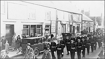 Members of the St John Ambulance Brigade parading past the Red Cow on Remembrance Day late 1920s