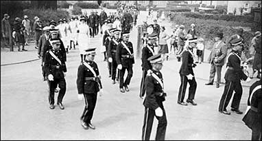 Members of St John Ambulance Brigade marching out of South Avenue into Station Road with members of the Fire Brigade following. c1925