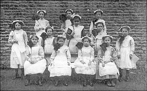 Photograph of Church School girls dressed as housemaids in 1900