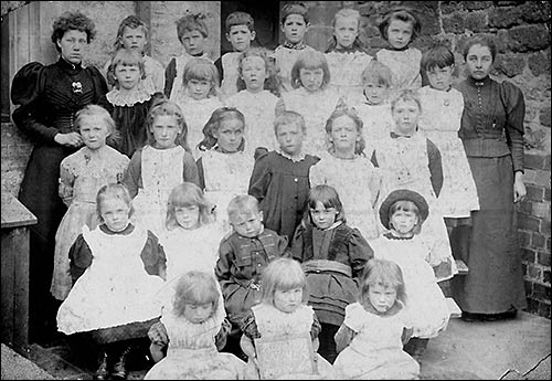 Photograph of pupils at Church Infant School with their teachers, Miss Drew and a teaching colleague