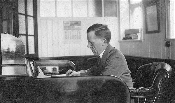 Photograph of Oliver Tailby at his desk in the office