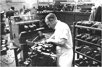 Photograph of Mr Hearn operatiing a machine in the Lasting Department
