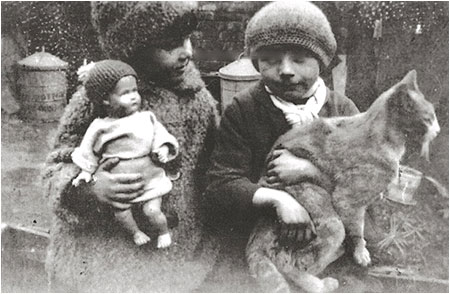 Photograph of Joan wearing her astrakhan coat and hat together with her friend, Kath Lewis holding the cat