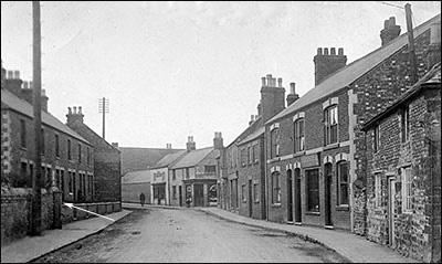 Another view of the High Street with the family home in the right foreground and the communal pump shown opposite.