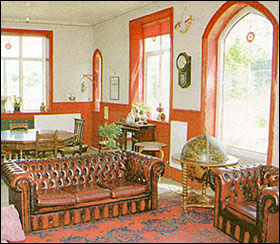 Photograph of the interior of the house depicting the lounge.