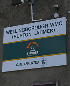 "Photograph of a sign on the side of the club bearing the words""Wellingborough WMC (Burton Latimer)""."