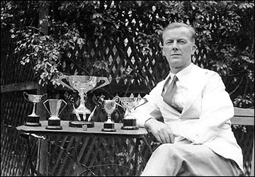 Albert Cooke with darts trophies