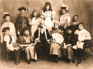 Photograph showing the cast of Cinderella: Standing: LtoR: George Talbutt, Arthur Barlow, Lucy Tailby, Nancy Loveday, Roland Boardman, Alfred Darby.  Seated: L to R: Frank Reynolds, Horace Miller, lJoe Whitney, Lily Blake, Wilf Downing, Frank Downing