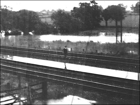 The Station Master Arthur Mutlow checking the flooded track in 1958