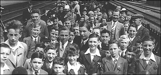 Photograph showing a joint school outing of pupils from the Church and the Council Schools  mid 1930s. Mr Fred Pentelow (deputy head of the Council School) and Mrs Pentelow are shown on the left and Mr Mitchell with Mr J Dunn of the Church School are on the right.