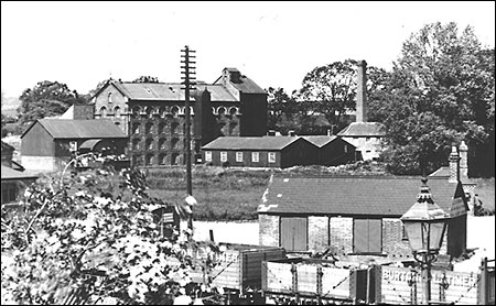 Photograph showing Burton Latimer Goods Yard in the 1930s with Weetabix Mills in the background.  Burton Latimer Co-op Society coal wagons are in the forefront.