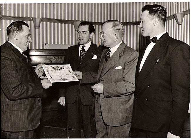 Bob Phillips receiving a British Legion Long Service Award from the branch president, Mr Frank T Peck.  Looking on are Dennis Long (centre back) and Fred Wells c1956