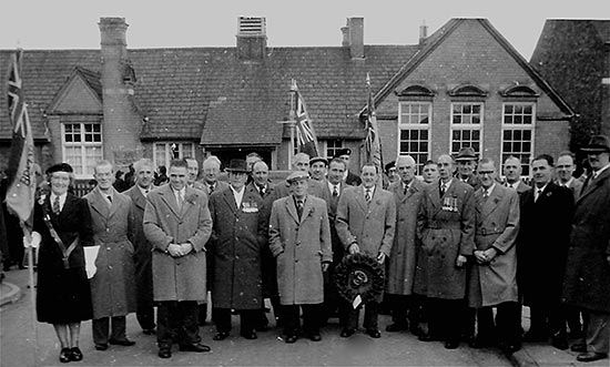 Members gathered for Remembrance Day parade c1950s with the Mission Room in the background.  L-R: Josie Crick, Mr T Hawkins, Mr A Buckby, Mr W Taylor, Mr Phillips, Mr F T Peck (President), Mr J Bull, Mr F Wells (almost hidden), Mr Prested, Mr J Blott (mostly hidden by Mr W T Brace Snr), Mr H Sawyer, Mr A Caffrey, ? standard bearer, Mr W A Brace Jnr, Dennis Crick (Legion Standard Bearer), Mr E Watson, Mr J Edwards, Mr A Byland, ?, ?, Mr L Blowfield, Mr F Pentelow, Mr H Dicks, Mr G Ward