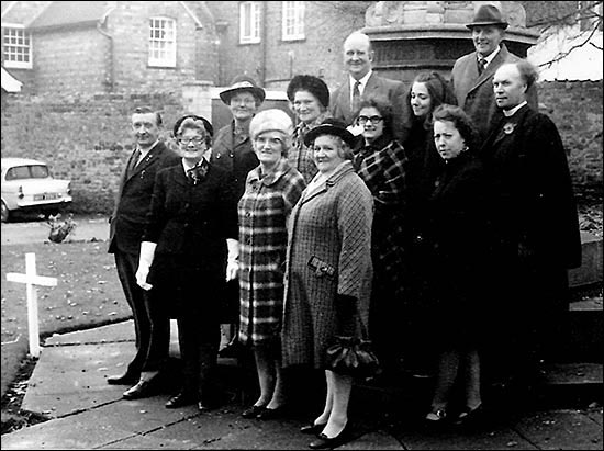 At the War Memorial after the 1973 Service of Remembrance. Standing at the back Arthur Knibbs and ? Second row: Mrs Nicholson, Mrs Joyce, Mrs Parfitt, Helen Featherstone, Margaret Heels, Revd Derek Taylor (Chaplain) Front row: Dennis Crick, Gwen Twelvetree, Josie Crick and Mrs Beach